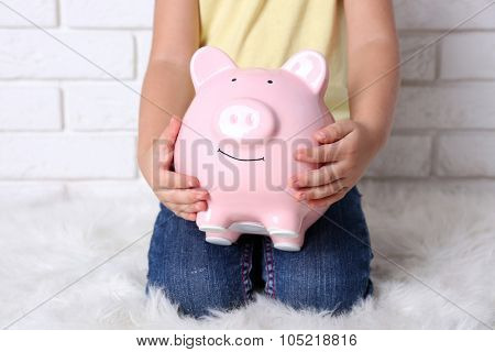Little girl with the pig  moneybox on brick wall background