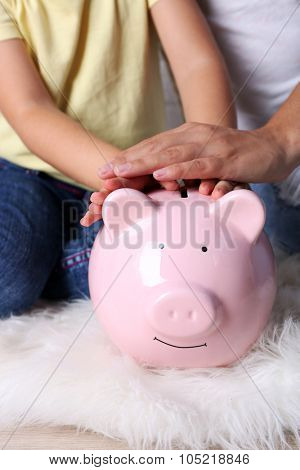Little girl with her mum and pig  moneybox closeup