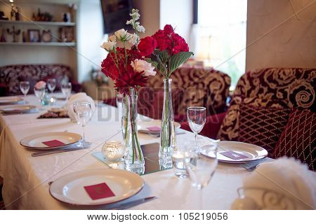 large table laid for Banquet, decorated in Burgundy tones