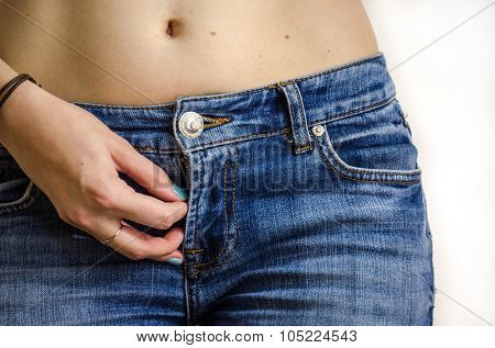 Jeans and a female hand with blue nail polish