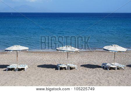 Greece. Kos. Kefalos Beach. Chairs And Umbrellas On The Beach