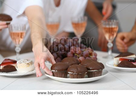 Friends hands with glasses of wine and desserts, close up