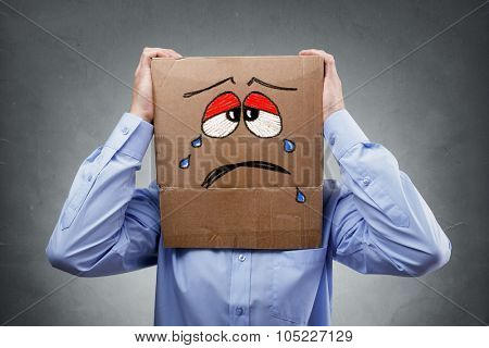 Businessman with cardboard box on his head showing a crying sad expression concept for headache, depression, sadness, heartache or frustration