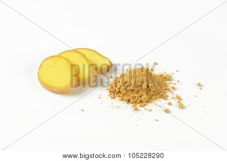 slices of fresh ginger and heap of ground ginger spice on white background