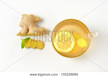 cup of ginger tea with lemon and fresh ginger on white background
