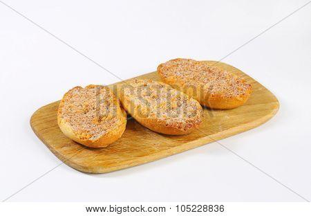 three cinnamon rusks on wooden cutting board