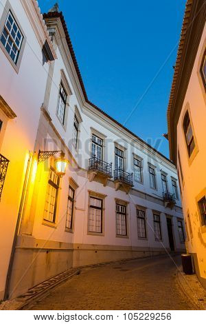 Narrow european street with paved road in the evening, buildings with balconies, Portugal