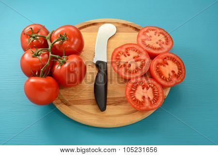 Cutting Vine Tomatoes With Knife On Wooden Board