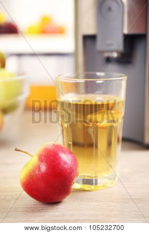 Juicer and apple juice on kitchen table