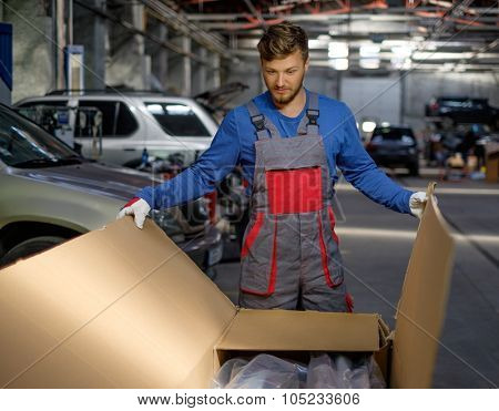 Mechanic opening box with new spare parts in a workshop