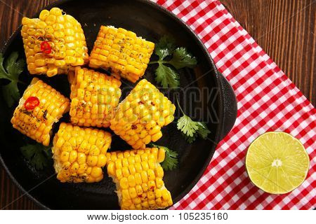 Tasty grilled corn and vegetables on black crockery decorated with plaid pattern cotton serviette