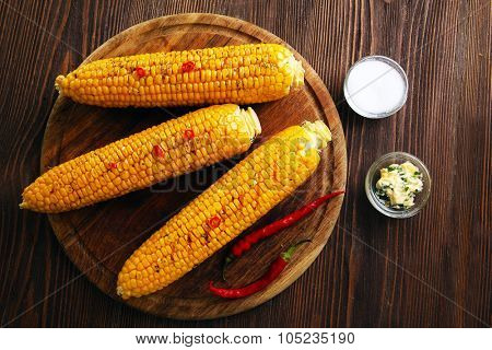 Grilled corn with hot pepper on rustic round plate on wooden background