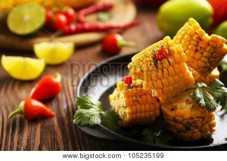 Tasty grilled corn and vegetables on black crockery