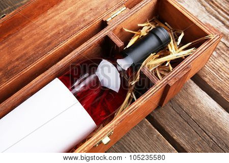 Expensive wine in elegant case with straw on wooden background