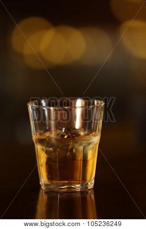 Whiskey glass tumbler standing on bar counter