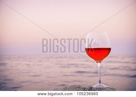 Romantic glass of wine sitting on the beach at colorful sunset