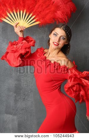 Beautiful woman in a red dress with a red fan in hand