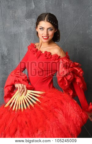 Beautiful dancer in a red dress with a red fan in hand