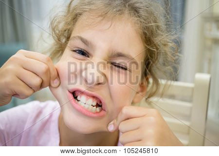 Close up view of beautiful grimacing teethy little girl.
