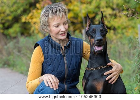 Smiling woman is looking to the dobermann in a park.