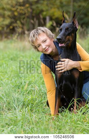 Woman is sitting on the grass behind a dobermann, focus on a dog.