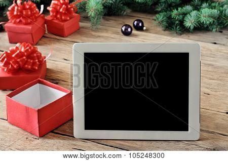 White Tablet Computer With Open Christmas Gifts On Wooden Table