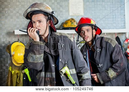 Male firefighter using walkie talkie at fire station with colleague standing in background
