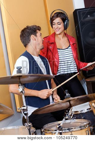 Smiling young woman holding digital tablet while looking at male drummer in recording studio