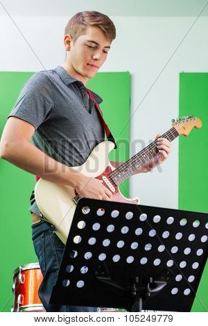 Young male guitarist performing while looking at musical notes in recording studio