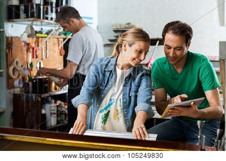 Mid adult male supervisor showing design on tablet computer to female employee using squeegee in paper factory