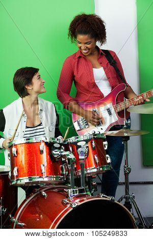 Happy female drummer and guitarist performing while looking at each other in recording studio
