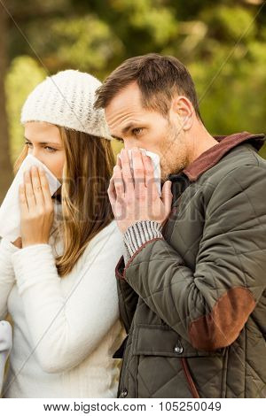 Sick couple blowing their noses on an autumns day