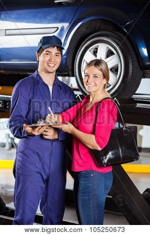 Portrait of happy mechanic with female customer while signing invoice in garage