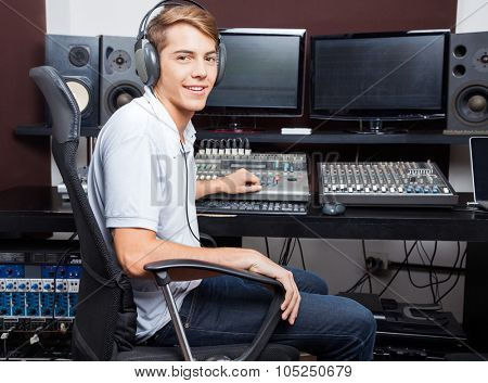 Side view portrait of smiling man mixing audio in recording studio