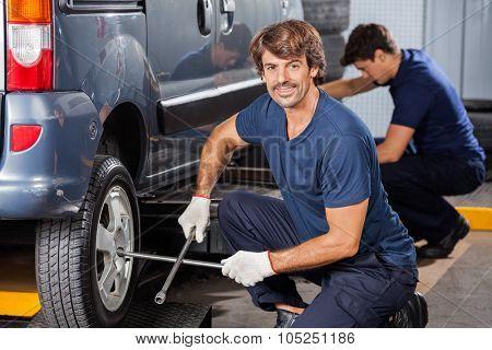 Portrait of confident male mechanic fixing car tire at auto repair shop
