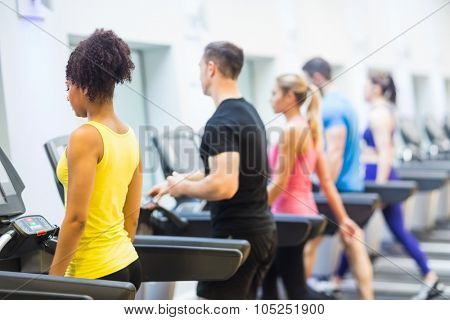 Fit people walking on treadmills at the gym