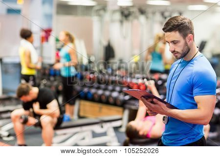 Handsome trainer looking at clipboard at the gym