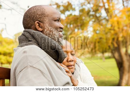 Peaceful senior couple sitting on a bench in parkland