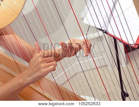 Detail of woman hands playing a harp with soft retro filter effect