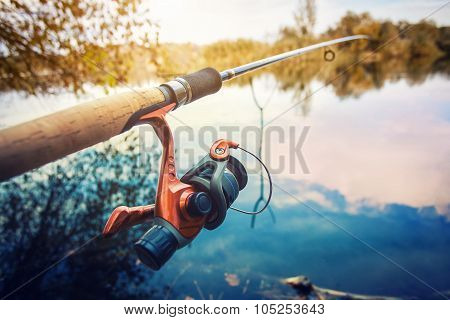 Fishing rod near pond in the morning
