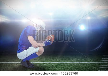 Profile view of American football player in attack stance against american football arena