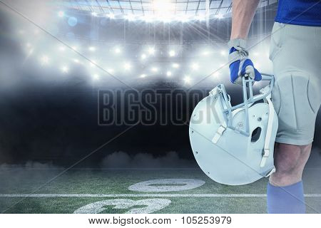 Close-up of American football player holding helmet against american football arena