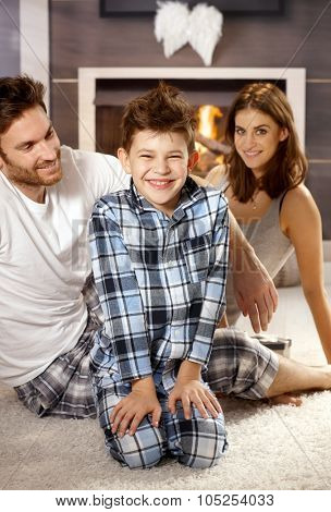 Morning photo of happy little family with mother father and little boy, all smiling.
