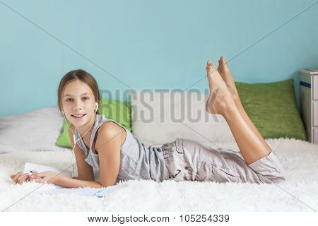Pre teen girl is relaxing in the bed and listening to music with earphones on the tablet at home