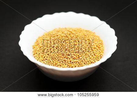 Organic yellow mustard in white bowl.