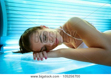 young woman laying on solarium bed and get brown skin tone ready for summer