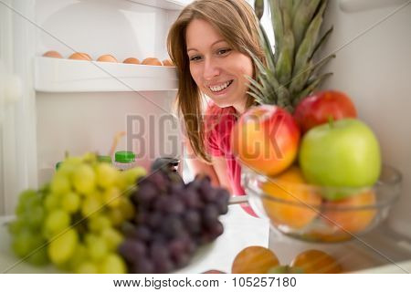 Smiling woman look at grape and apple in refrigerator