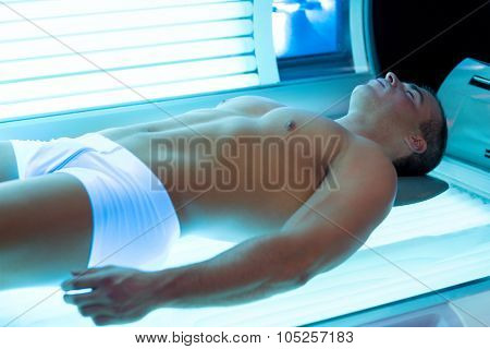 Attractive man in solarium enjoying sunbathing on tanning bed