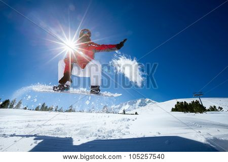 Snowboarder in the air with beautiful  blue sky in background