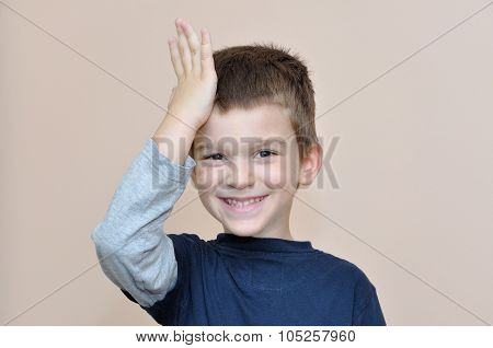 Young boy slapping hand on head